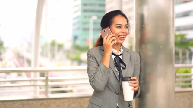 vidéos et rushes de stand de femme d'affaires et parler affaires avec le smartphone ou téléphone portable en ville. - directrice
