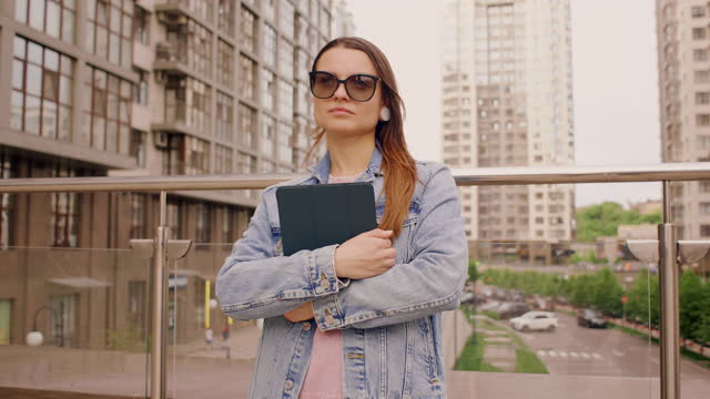 vidéos et rushes de business woman stands holding a tablet feels confident - 25 29 years