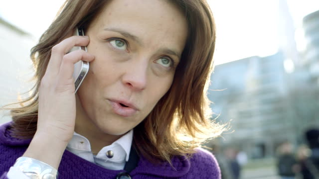 stockvideo's en b-roll-footage met business woman takes a call outside offices - middellang haar