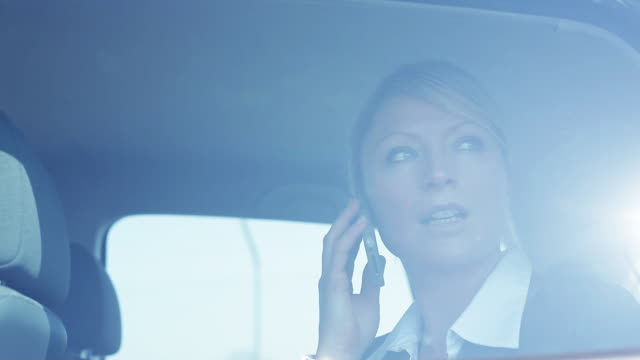 MS Business woman talking on phone looking at plane through car window / Albi, Midi-Pyrennees, France