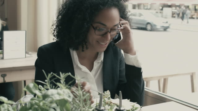 vídeos de stock, filmes e b-roll de business woman talking on smart phone during lunch break, laughing, eating salad - excesso de trabalho