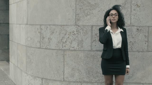 vídeos de stock e filmes b-roll de business woman talking on smart phone outside of office building - saia