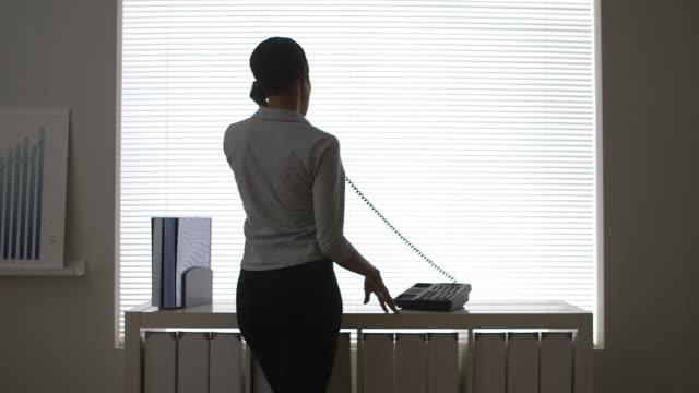 stockvideo's en b-roll-footage met business woman talking on telephone in front of window - telefoonhoorn