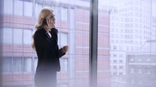 vídeos y material grabado en eventos de stock de mujer de negocios hablando por teléfono en el pasillo de un negocio moderno edificio en el centro de la ciudad - esmalte de uñas rojo