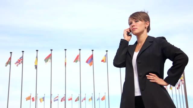 vidéos et rushes de femme d'affaires au téléphone - poteau d'appui