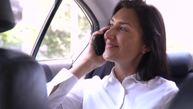 Business woman talking phone in car