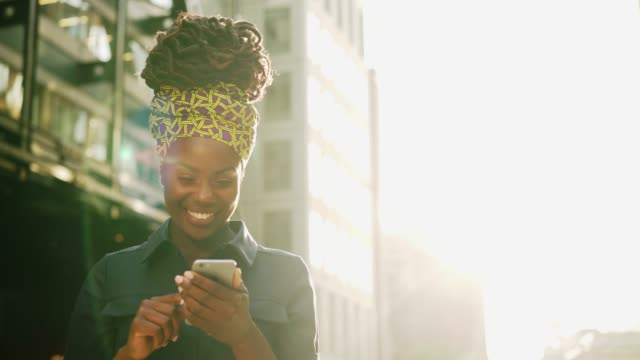 business woman text messaging on smart phone, sunset, lens flare - scrolling stock videos & royalty-free footage