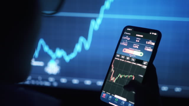 vídeos de stock, filmes e b-roll de mulher de negócios negociando mercado de ações em telefone inteligente com tela financeira do mercado de ações em segundo plano - casa de câmbio