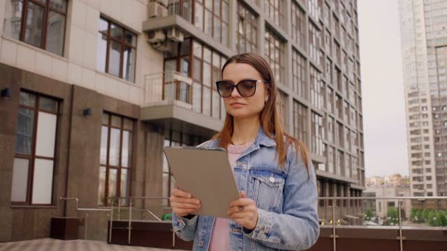 vidéos et rushes de business woman typing and sending text message from her tablet in walking in the city - 25 29 years