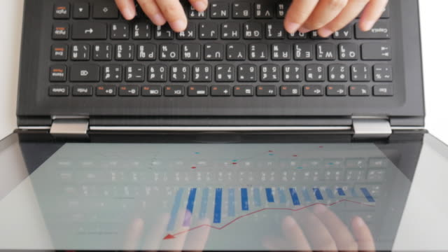 Business woman typing on laptop keyboard and analyzing graph on laptop