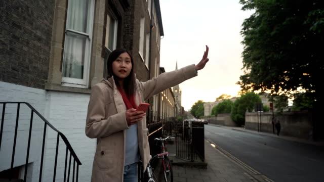 vídeos y material grabado en eventos de stock de uhd : mujer de negocios utilizar aplicación en el teléfono móvil para el taxista de llamadas - llegada