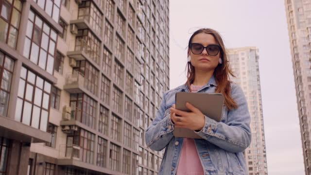 vidéos et rushes de business woman uses tablet on city background - 25 29 years