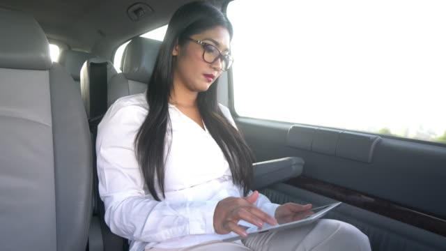 donna d'affari utilizzando la tavoletta digitale e smartphone - sedile del passeggero video stock e b–roll
