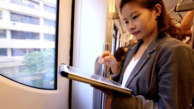 business woman  using digital tablet computer in electric train - tjänstekvinna bildbanksvideor och videomaterial från bakom kulisserna