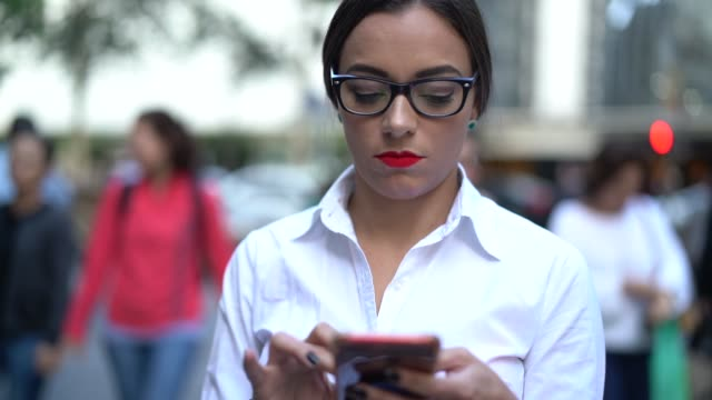 vídeos de stock, filmes e b-roll de mulher de negócios usando móveis na rua da cidade - só uma mulher de idade mediana