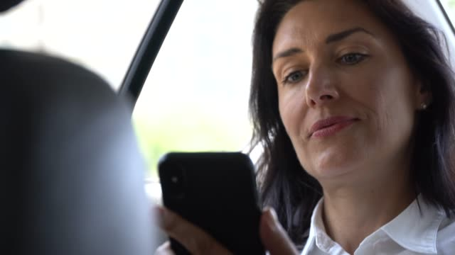 business woman using phone in car - taxi video stock e b–roll