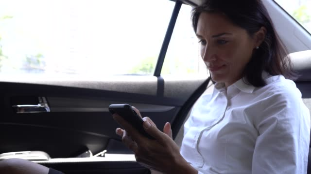 business woman using phone in car - businesswoman stock videos & royalty-free footage