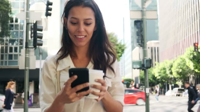 business woman using smart phone and drinking coffee on the go - on the move stock videos & royalty-free footage