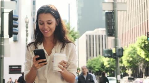 affärs kvinna med hjälp av smart telefon och dricka kaffe på språng - pendlare bildbanksvideor och videomaterial från bakom kulisserna