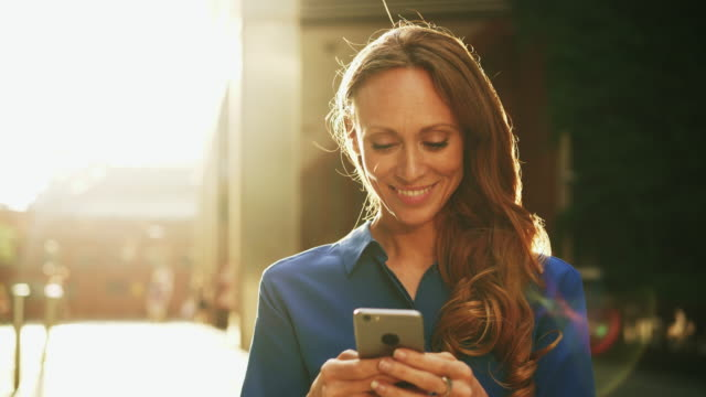 business woman using smart phone at sunset - iphone stock-videos und b-roll-filmmaterial
