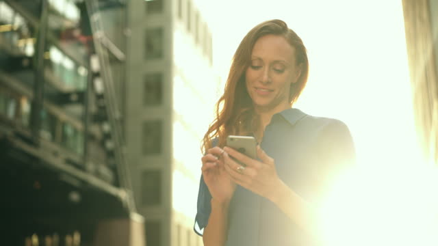 vídeos de stock e filmes b-roll de business woman using smart phone sunset - texto