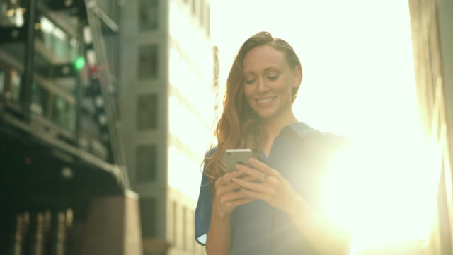 business woman using smart phone sunset - vorderansicht stock-videos und b-roll-filmmaterial