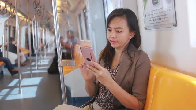 business woman using smartphone on city train - treno della metropolitana video stock e b–roll