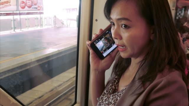 vídeos de stock, filmes e b-roll de mulher de negócios usando o smartphone no trem da cidade - trem do metrô