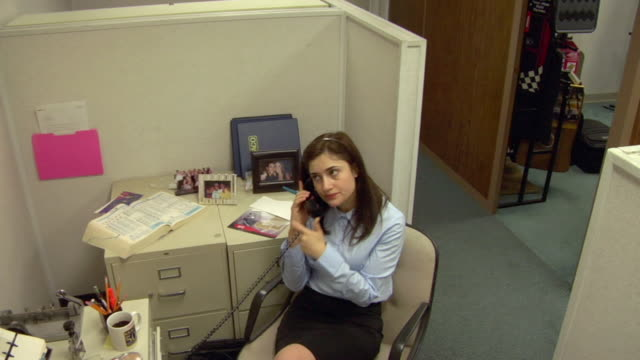 MS, HA,  Business woman waiting on phone making faces, colleague walking past office cubicle, Compton, California, USA