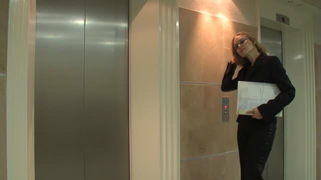 ビジネスの女性ウェイツのリフトのオフィス - 若い女性だけ点の映像素材/bロール