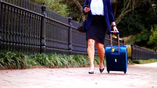 business woman walking down sidewalk pulling suitcase. - skirt stock videos & royalty-free footage
