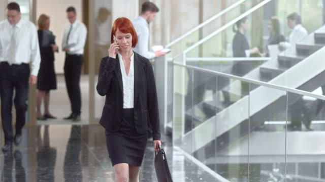 ds business woman walking down the hallway - dolly shot stock videos & royalty-free footage