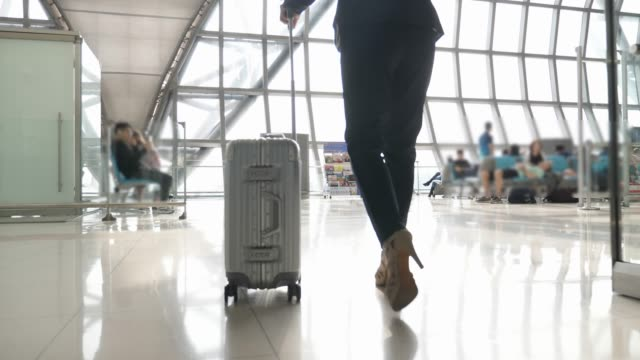 business woman walking with travel bag in the airport terminal or subway - airport stock videos & royalty-free footage