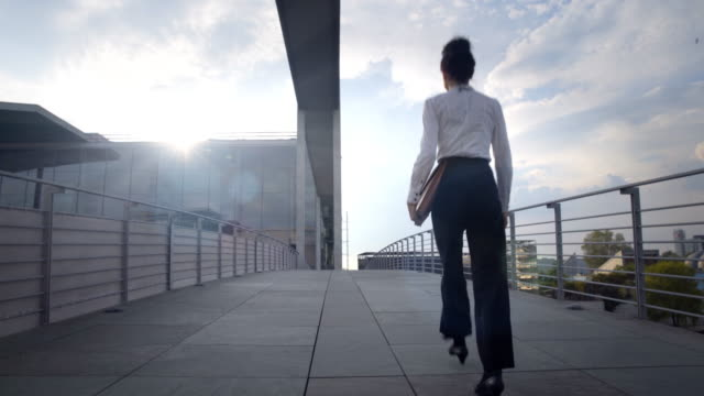 business woman walks over pedestrian bridge - geschäftsfrau stock-videos und b-roll-filmmaterial