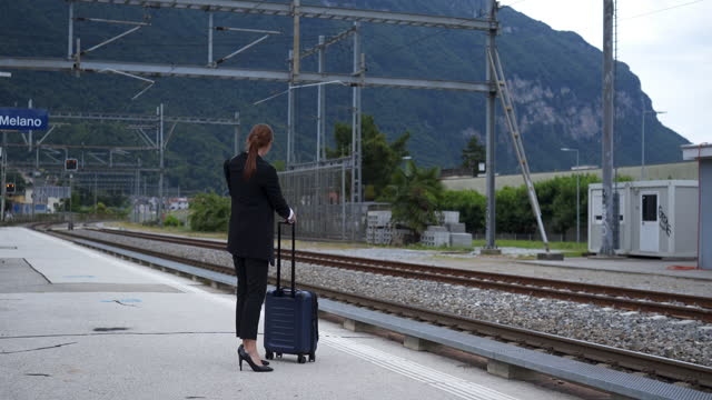 business woman walks towards a train platform and checks phone - luggage stock videos & royalty-free footage