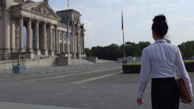 vídeos de stock e filmes b-roll de business woman walks towards the reichstag - politician