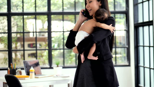 business woman with baby working at home - working mother stock videos & royalty-free footage