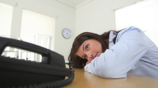 Business woman with head on desk waiting for telephone call