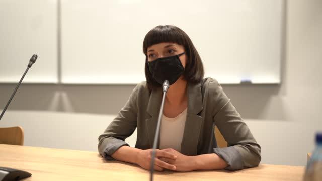 vídeos y material grabado en eventos de stock de mujer de negocios con máscara protectora de la cara hablando con la audiencia durante la conferencia - enseñar