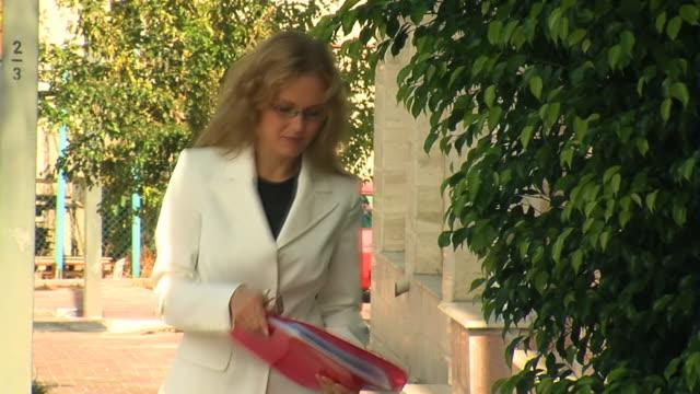 ビジネスの女性をフォルダに路上で赤 - 若い女性だけ点の映像素材/bロール