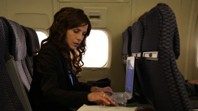 MS Business woman working on laptop in plane / Los Angeles, California, United States