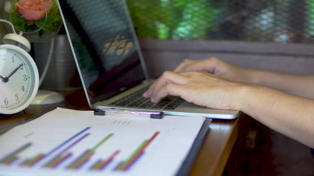 Business woman working on paper and using laptop for making report at office