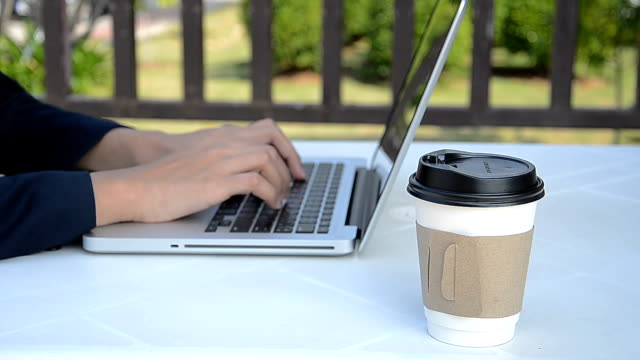 Business woman working with  laptop (notebook) and drinking hot coffee.