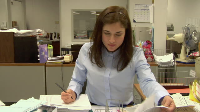 ms, business woman writing sitting at desk in office while colleague walking on hands behind her, compton, california, usa - office politics stock videos & royalty-free footage