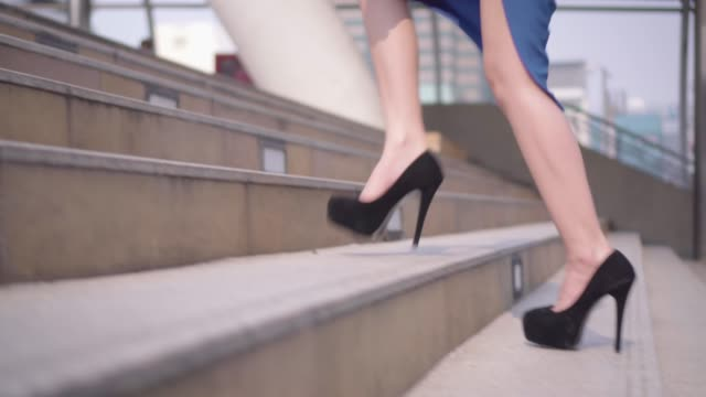 vídeos de stock e filmes b-roll de business woman's legs stepping up on stairway stepping in city. - passos