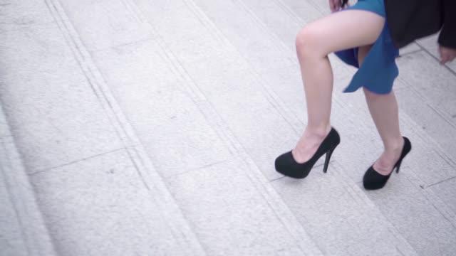vidéos et rushes de jambes de femme d'affaires intensifier sur escalier pas à pas dans la ville. - beaux pieds et femme