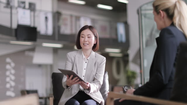 business women in a meeting looking at a digital tablet - 40代点の映像素材/bロール
