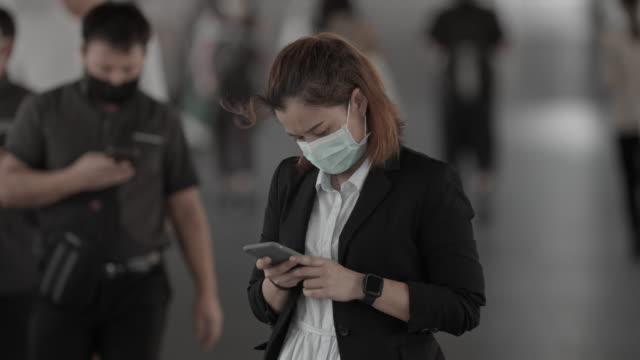 vidéos et rushes de femmes d'affaires dans le stand protecteur de masque de visage et utilisant le smartphone dans la foule, mouvement lent - masque de chirurgien