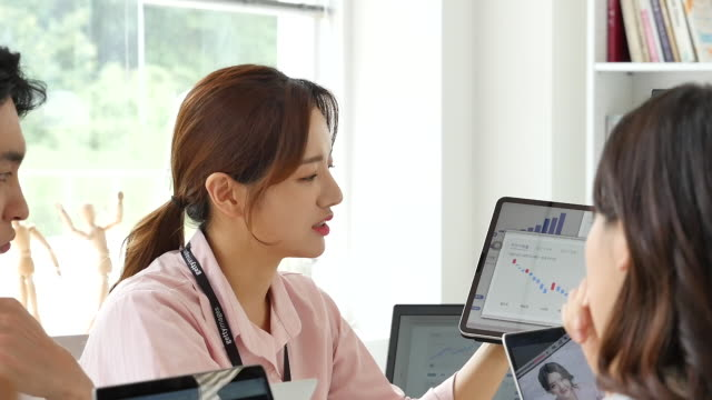 mcn business - young woman explaining data from tablet computer - ため息点の映像素材/bロール