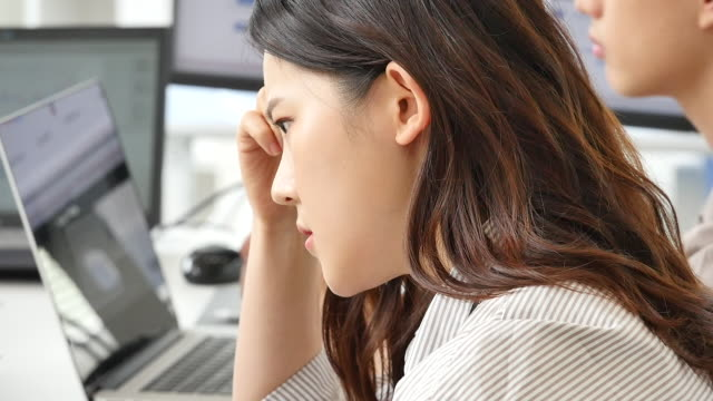 mcn business - young woman feeling stressed at work - 真剣点の映像素材/bロール